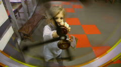 Little girl spins pendulum mechanism in glass frame - stock footage