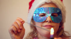 Little girl in holiday mask conflagrates bengal fire Stock Footage