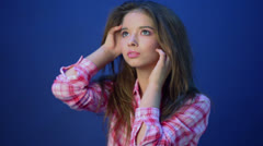 Pretty girl in pink plaid shirt touches her head when poses Stock Footage