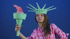 Girl in pink shirt holds torch in crown of statue of liberty Stock Footage