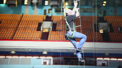 Worker climbs down by rope ladder in stadium with people Stock Footage