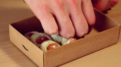 Hand puts cookies with almond nut and sugar powder in small box Stock Footage