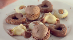 Hand strews chocolate crumbs on several kinds of cookies Stock Footage