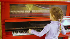 Stock Video Footage of Little girl plays on red piano with transparent case