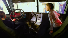 Boy sit in car on driver place with sister at passenger chair Stock Footage
