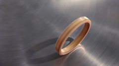 Golden ring roll by metal disk surface which spins, closeup Stock Footage