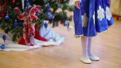 Kids in holiday costumes dance around girl near christmas tree Stock Footage