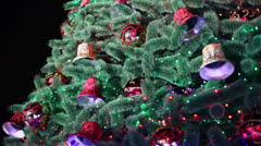 Garland lamps blink on christmas tree with toy balls and bells - stock footage