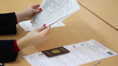 Woman turn page of voting rules booklet with passport - stock footage