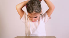Little girl sits at table and ties her hair with rubber bend Stock Footage
