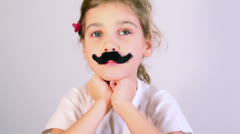 Little girl with glued fake black mustaches speaks and gestures Stock Footage