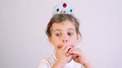 Little girl eats colorful candy with crown on head Stock Footage