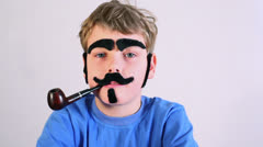 Little boy with pipe, fake mustache, eyebrows, and sideburns Stock Footage