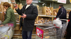 People buy bread at Auchan store in shopping center Troika Stock Footage