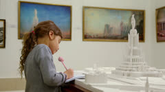 Girl draws near project of Palace of Soviets during excursion Stock Footage