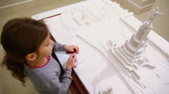 Little girl draws near miniature of project of Palace of Soviets - stock footage