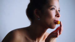 Attractive young model bites fruit and poses, closeup Stock Footage