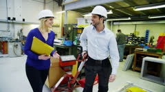 Cheerful warehouse workers chat together as they go about their work Stock Footage