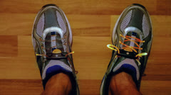Mans feet in sport shoes with flashing laces at parquet floor Stock Footage