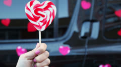 Hand holds candy in form of heart near offroader with stickers Stock Footage