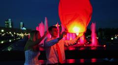 Newlyweds hold japanese lantern near illuminated fountain Stock Footage