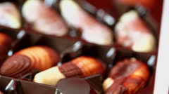 Chocolate appetizing candies in form of seashell slide at box Stock Footage