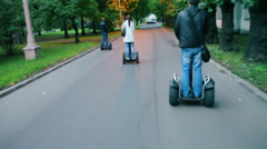 Young people ride on segways by alley in park at evening Stock Footage