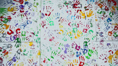 Colorful imprints of palms on wall, shown in motion Stock Footage