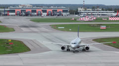Aircraft turns on runway at airport with service car traffic - stock footage
