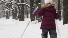 Two kids moving away from the camera on ski near forrest - stock footage