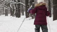 Two kids moving away from the camera on ski near forrest Stock Footage