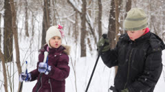 Two kids with ski poles staying and talking near forrest - stock footage
