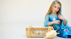 Little girl in mermaid costume resting on a box isolated Stock Footage