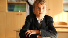 Boy sitting at his desk in first day of school Stock Footage