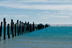 Beautiful rotten mooring on a beach where only the pillars are left over Stock Photos