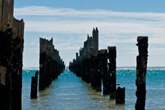 beautiful rotten mooring on a beach where only the pillars are left over - stock photo