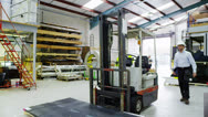 Male forklift truck driver arrives on shift to take over from a female worker Stock Footage