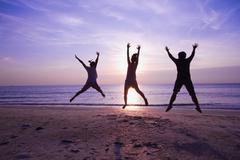 family jumping on the beach on beautiful sunrise, silhouette shot - stock photo
