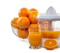 juice extractor with juice and ripe oranges - stock photo