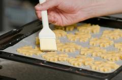 Glazing cookies before backing on backing paper in a tray Stock Photos