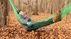 Cute little boy swinnging in green hammok smiling Stock Footage