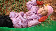 Cute little girl swinging in hammok, moving camera Stock Footage