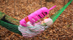 Cute little girl swinging in hammok playing with a phone toy Stock Footage