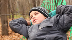 Cute boy swinging in hammok smiling, torso view Stock Footage