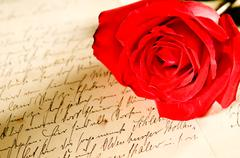 Red rose over a hand written letter Stock Photos