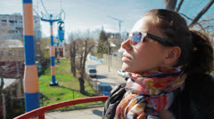 Girl in sunglasses rides through the city on the cable car Stock Footage