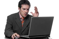 Stock Photo of young bored man and working with is laptop