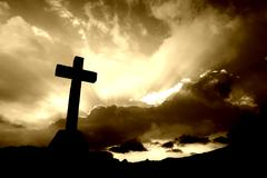 christian cross silhouette and the clouds in sepia tone - stock photo