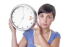 Caucasian young woman holding a big clock Stock Photos