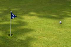 Ball and flag in a green golf field Stock Photos